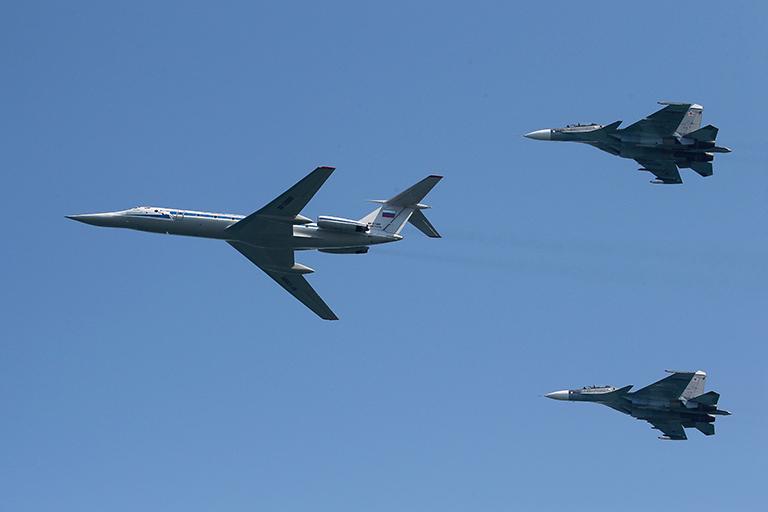 На фото: самолет Ту-134 (слева) в сопровождении многоцелевых истребителей Су-30СМ во время авиационной части военно-морского парада в честь Дня ВМФ России.