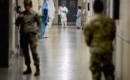 На фото: специалисты по биологическим наукам (на заднем плане) в защитной одежде для биобезопасности при лечении вирусных заболеваний в Командовании медицинских исследований и разработок армии США в Форт-Детрике, штат Мэриленд. 9 марта 2020